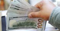 Мужчина держит долларовые купюры. Архивное фото