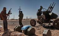 Бойцы оппозиции стоят на дороге в городе Рас-Лануф в Ливии. Архивное фото