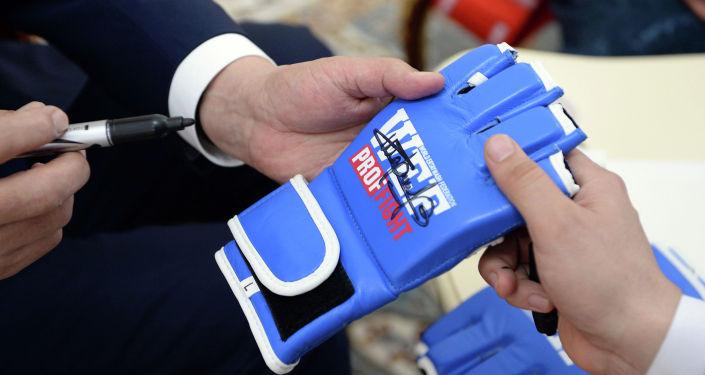 Президент Кыргызской Республики Сооронбай Жээнбеков подписывает перчатки во время встречи с чемпионкой мира по смешанным единоборствам по версии UFC Валентиной Шевченко.