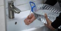 Мужчина наливает с тары, чтобы помыть руки в уборной. Архивное фото