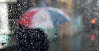 Девушка с зонтом идет по улице во время дождя. Архивное фото
