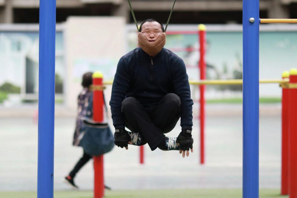 Упражнения Сунь Жунчуня с импровизированным шейным тяговым устройством, прикрепленным к высокой планке в спортивном комплексе в Шеньяне