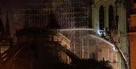 Пожарные во время тушения крупного пожара в здании собора Парижской Богоматери в Париже. 16 апреля 2019 года