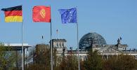 Флаги Германии, Кыргызстана и Евросоюза на фоне здания Рейхстага в Берлине. Архивное фото