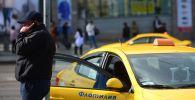 Водитель такси разговаривает по телефону. Архивное фото