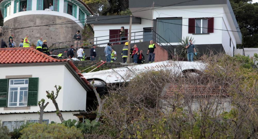 Спасатели стоят рядом с обломками автобуса после аварии в Канико на португальском острове Мадейра, 17 апреля 2019 года