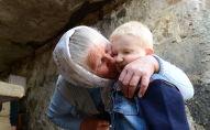 Пожилая женщина целует ребенка. Архивное фото