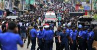 Полицейские Шри-Ланки расчищают дорогу, когда машина скорой помощи проезжает с ранеными во время церковных взрывов в Коломбо, Шри-Ланка, в воскресенье, 21 апреля 2019