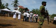 Солдат стоит на страже во время массового захоронения жертв, через два дня после череды нападений террористов-смертников на церкви и отели по всему острову в пасхальное воскресенье на кладбище возле церкви Св. Себастьяна в Негомбо. Шри-Ланка, 23 апреля 2019 года