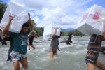 Индонезиянын Түштүк Сулавесинде жумушчулар шайлоо урнасын дарыядан ташып өткөзүүдө. Архивдик сүрөт