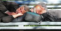 Мужчины спят на скамейке. Архивное фото