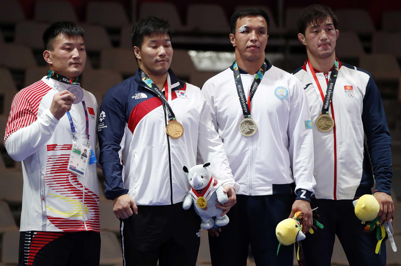 Обладатель золота Чо Хё Чул из Южной Кореи, серебряный призер Сяо Ди из Китая и бронзовые призеры из Кыргызстана Узур Джузупбеков и Ерулан Искаков из Казахстана во время награждения в Азиаде. Джакарта