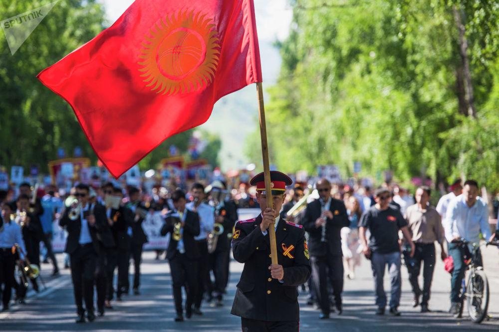 Кыргызстандын желегин көтөргөн аскер