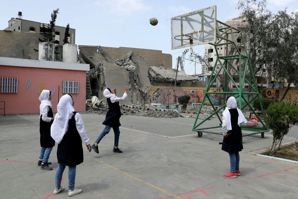 Школьницы играют в баскетбол возле разрушенного в результате авиаударов здания в секторе Газа (Палестина)