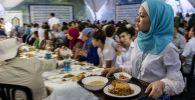 Девушка разносит еду во время ифтара (вечернего приема пищи). Архивное фото