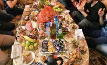 Мусульмане за столом (дастарханом) на праздновании ооз ачар. Архивдик сүрөт