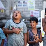 Дети играют с монетками на празднике Святой Риты Кашийской в Маниле.