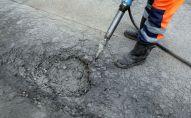 Рабочий во время ремонтных работ дорожного покрытия. Архивное фото
