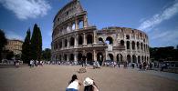 Туристы делают фотографии Колизея в Риме