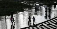 Люди идут по улице во время дождя. Архивное фото