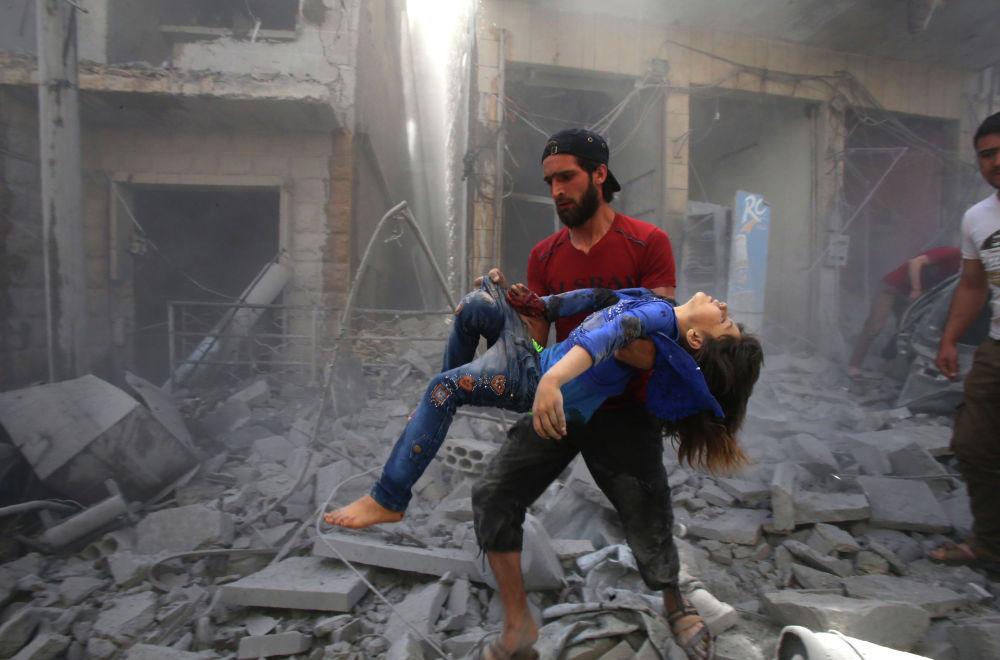 Мужчина уносит девочку, пострадавшую в результате взрыва бомбы в сирийской провинции Идлиб. В течение последнего месяца боевые действия в провинциях Идлиб и Северная Хама привели к 160 жертвам среди гражданского населения и перемещению более 200 тысяч человек.