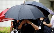 Женщины с зонтами идут по улице во время дождя. Архивное фото