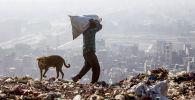 Индиец отбирает вещи на переработку в Нью-Дели, Индия