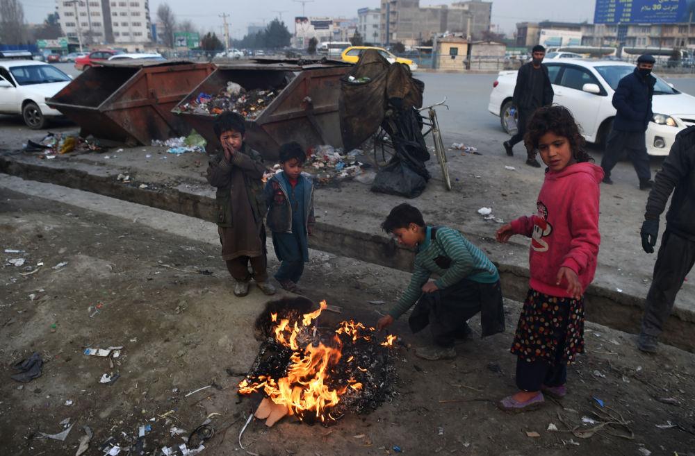 Афган балдар Кабулга кетчү жолдун четинде желим өрттөп жылынууда