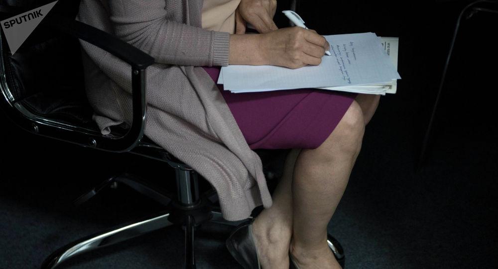 Женщина пишет на листе бумаги сидя в кресле. Архивное фото