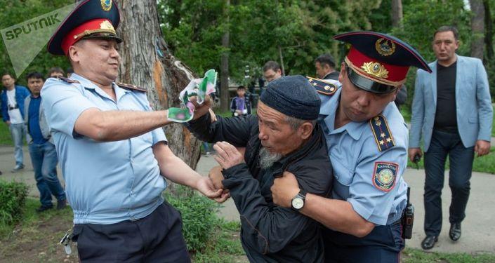 Сотрудники полиции задерживают участника несанкционированного митинга  в день проведения выборов президента Казахстана в Алма-Ате.