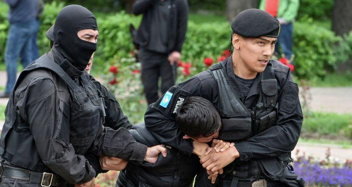 Полицейские задерживают сторонника оппозиции во время акции протеста против президентских выборов, в Алматы. Казахстан, 9 июня 2019 года