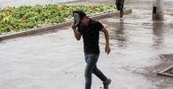 Парень укрывается от дождя в Бишкеке. Архивное фото