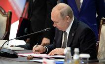 Владимир Путин подписывает документ. Архивное фото