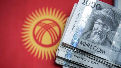 Одна тысячные сомовые купюры на фоне флага Кыргызской Республики