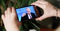 Россия президенти Владимир Путиндин түз алып берүүсүн көргөн кыз. Архивдик сүрөт