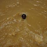 Суданский парень спасается от жары в ирригационном канале