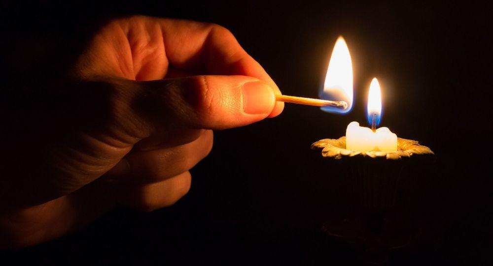 Мужчина зажигает свечу. Архивное фото