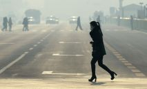 Девушка в маске переходит дорогу. Архивное фото