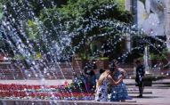 Девушки делают селфи на фоне фонтана на площади Ала-Тоо в Бишкеке