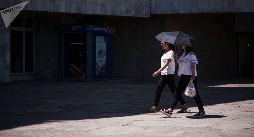 Девушки с зонтом идут во время жаркой погоды в Бишкеке. Архивное фото
