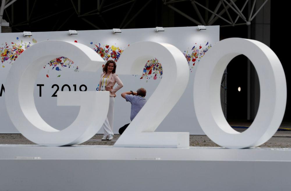 Женщина позирует фотографу возле логотипа саммита G20 в Осаке