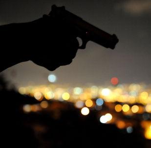 Мужчина с пистолетом  одной из трущоб с самыми высокими показателями городского насилия в Медельине, Колумбия. 21 января 2010 года