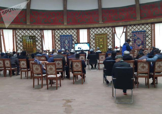 Люди смотрят телевизор  в пресс-центре штаба СДПК, около дома бывшего президента КР Алмазбека Атамбаева в селе Кой-Таш