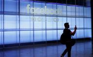 Мужчина на фоне логотипа Facebook. Архивное фото