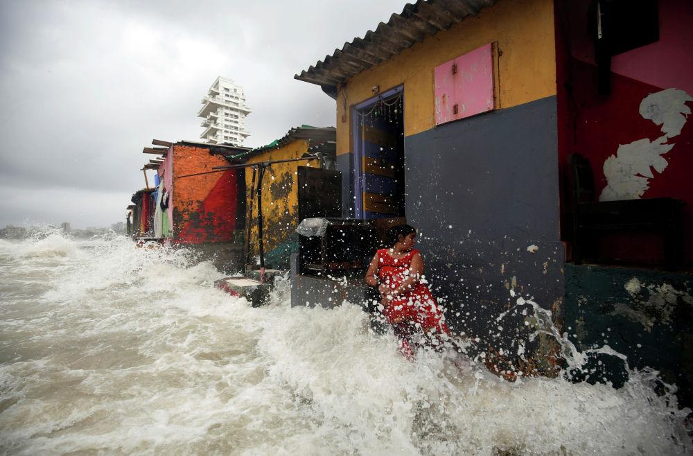 Огромные волны на берегу моря обливают женщину во время прилива в Мумбаи. Индия, 4 июля 2019 года