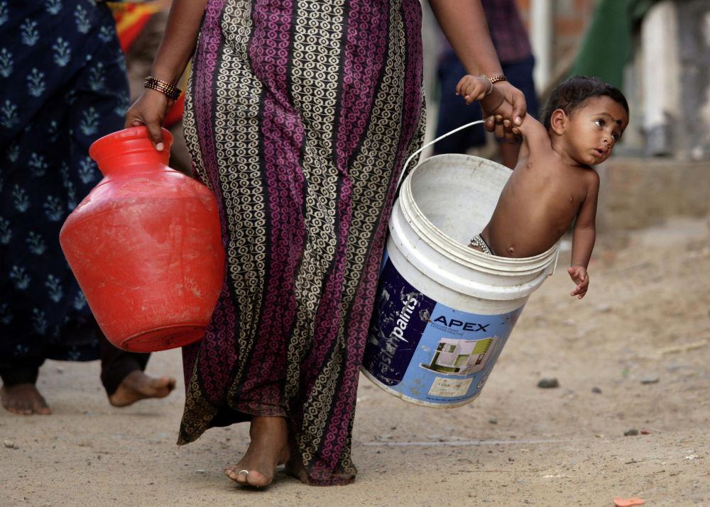 Женщина несет своего сына в ведре после сбора воды на окраине Ченнаи. Индия, 4 июля 2019 года