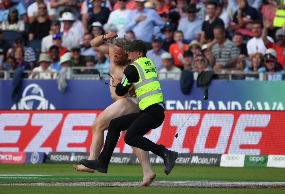 Сотрудник службы безопасности задерживает мужчину, выбежавшего на поле во время Чемпионата мира по крикету