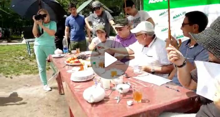 Руководитель отдела маркетинга ОАО Айыл Банк Нуриля Чекирова опубликовала в Facebook фотографию, где видно, что над головой председателя правления Бактыбека Шамкеева держат зонт