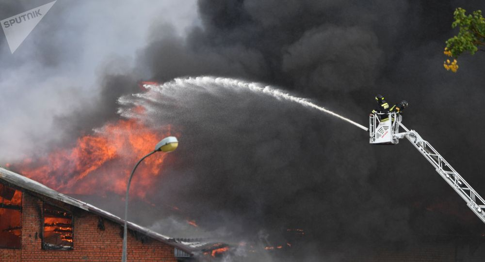 Сотрудники противопожарной службы МЧС РФ во время тушения пожара в здании около Северной ТЭЦ в Мытищах.
