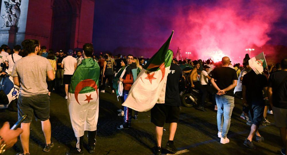 Алжирские болельщики празднуют победу их команды на четвертьфинале футбольного матча Кубка наций Африки (CAN) 2019 между Кот-д'Ивуаром и Алжиром около Триумфальной арки в Париже, 11 июля 2019 года